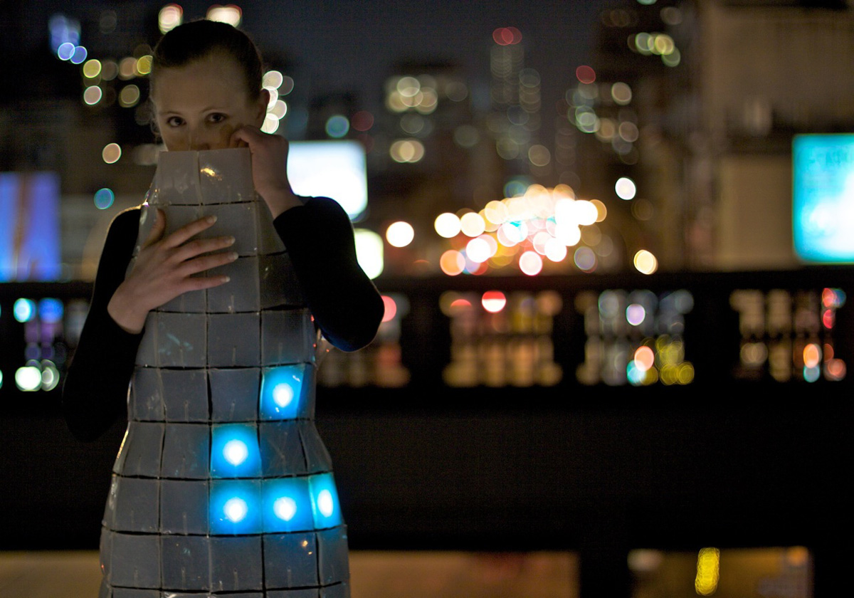Elizabeth Fuller wearing the game of life dress on the High Line with car headlights in the background.