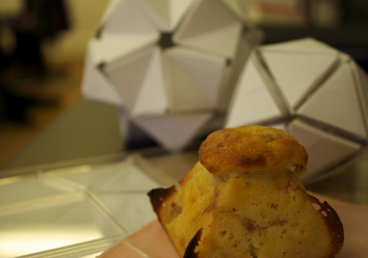 Photograph of a square based pyramid muffin resting on top of it's silicon baking container and the Plexiglas mold used for casting. Concept models rest in the background.